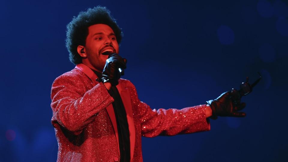 Vêtu d'une veste rouge, The Weeknd chante dans un micro sur scène.