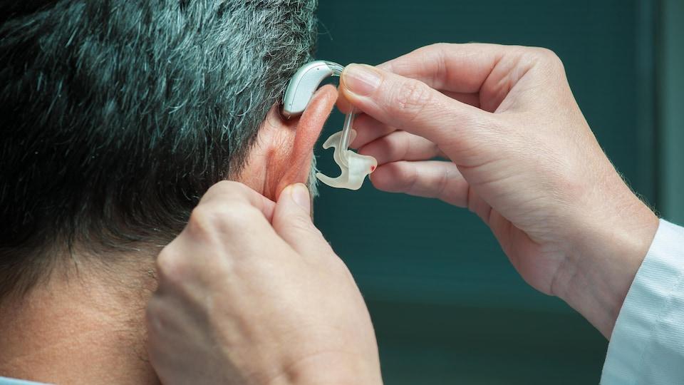 Un médecin insère une prothèse auditive dans l'oreille d'un homme.
