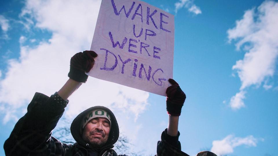 Un homme tient une affiche sur laquelle on lit : « Réveillez-vous, nous mourons », en anglais.