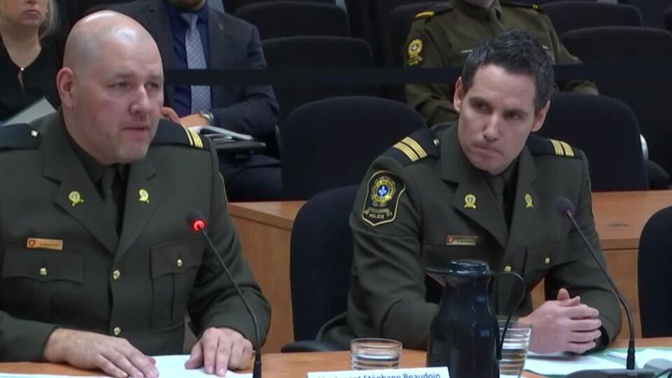 Deux policiers en uniforme assis dans une salle d'audience pour témoigner.