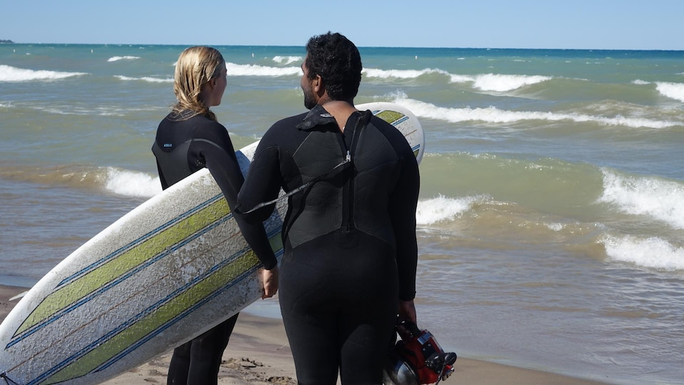 Deux surfeurs sur la plage regardent les vagues.