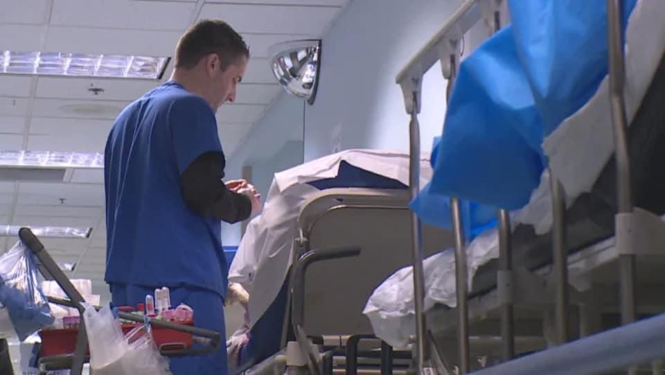 Un infirmier près d'un patient allongé dans un lit se trouvant dans un couloir.