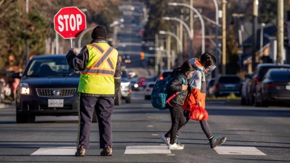 Deux enfants traversent un passage pour piétons pendant qu'un agent tenant un panneau d'arrêt stoppe la circulation routière.
