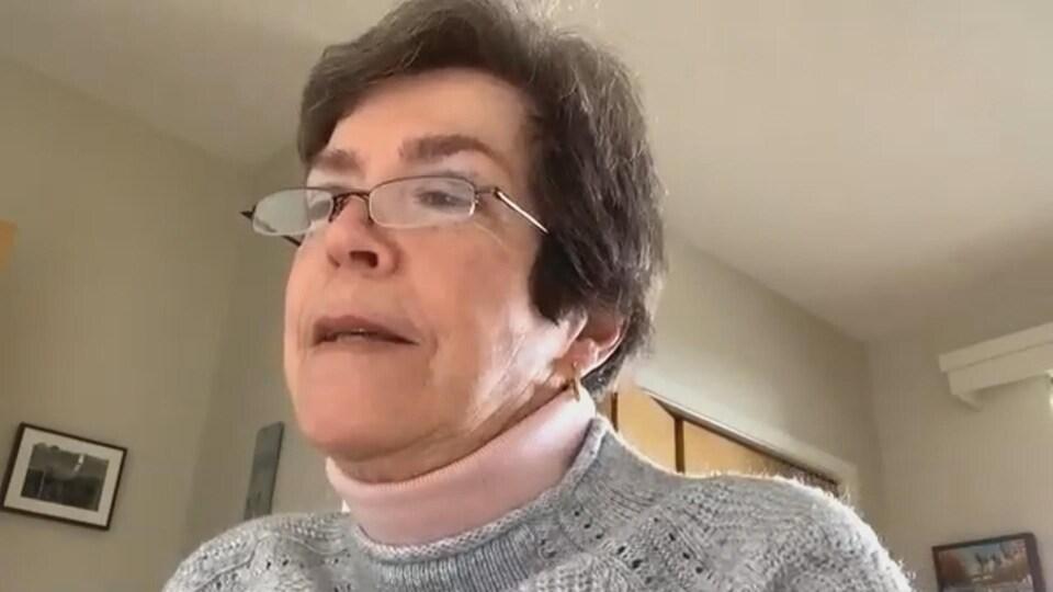 Une femme regarde de profil. Elle porte des lunettes.