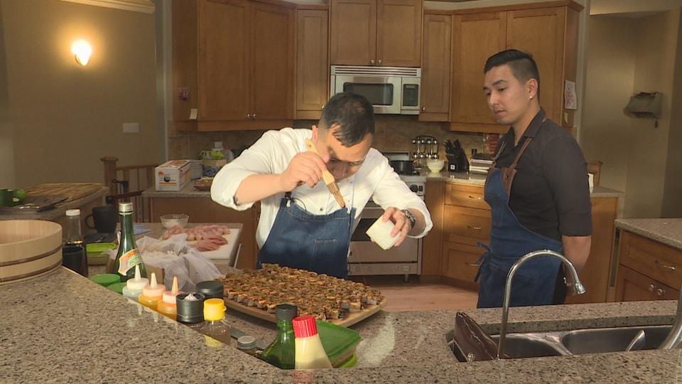 Le chef sushi Vinh Tran et son assistant Izac Harry dans une cuisine.