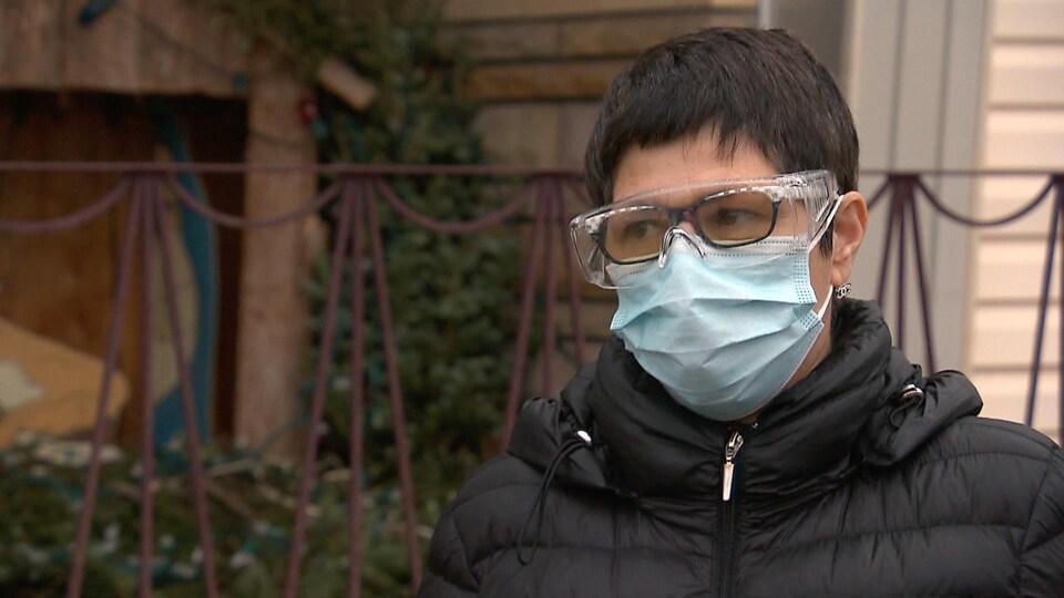 Plan rapproché de Suzanne Côté, avec un masque et des lunettes de protection