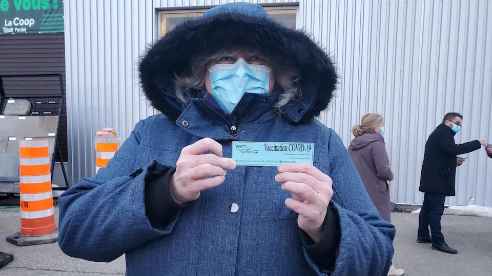 Une femme avec un masque montre son coupon à la caméra.