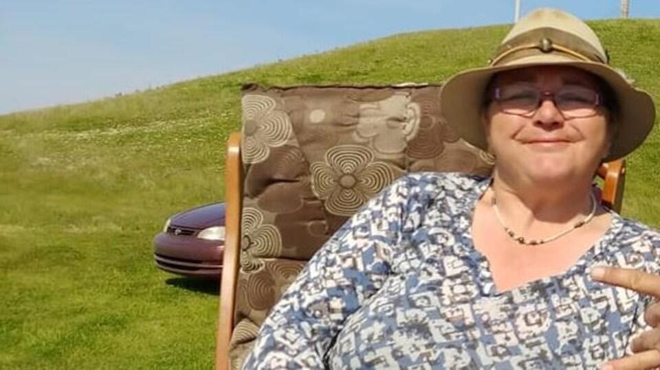 Suzanne René est photographiée à l'extérieur, devant une butte verdoyante avec un chapeau sur la tête.