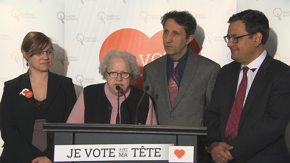 Suzanne Tremblay parle au micro d'un lutrin, entourée de Marie-Neige Besner et d'Amir Khadir.