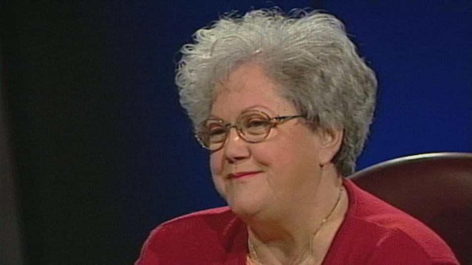 Suzanne Tremblay est assise à une table et sourit.