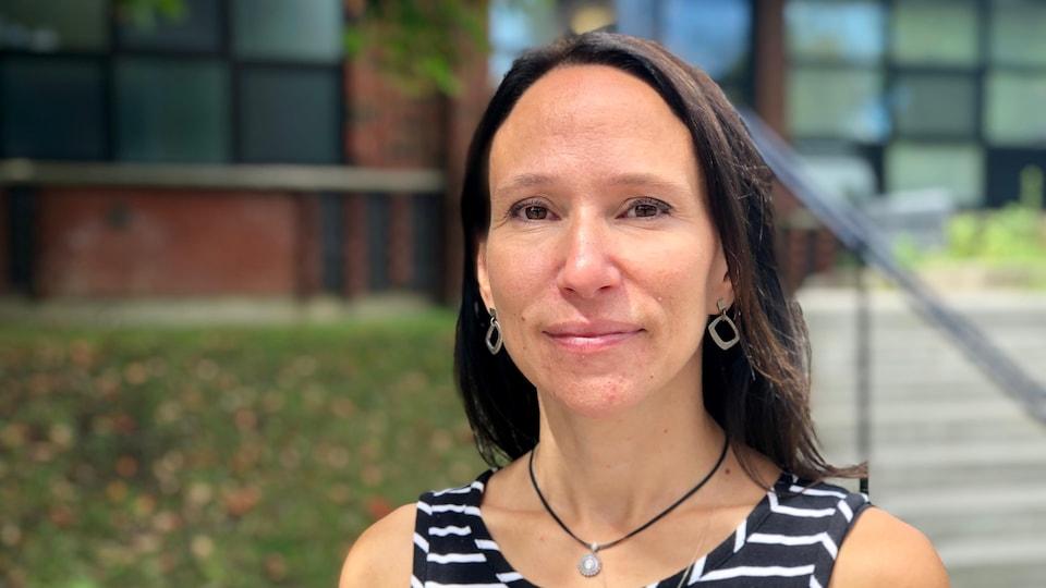 Suzanne Tremblay pose pour la caméra devant une école.