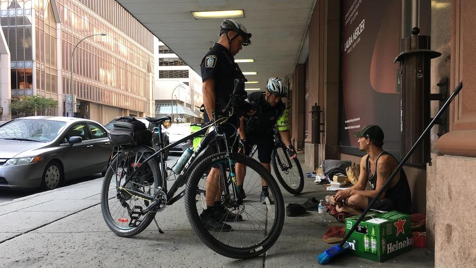 Deux policiers près de leur vélo discutent avec un itinérant assis sur le trottoir.