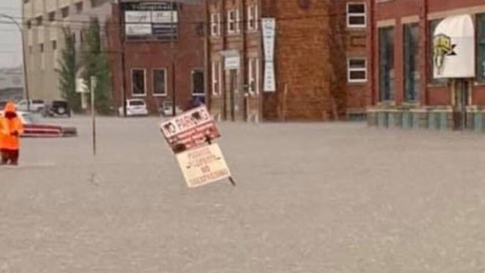 Vue d'une rue inondée de Swift Current, une personne debout a de l'eau jusqu'aux genoux.