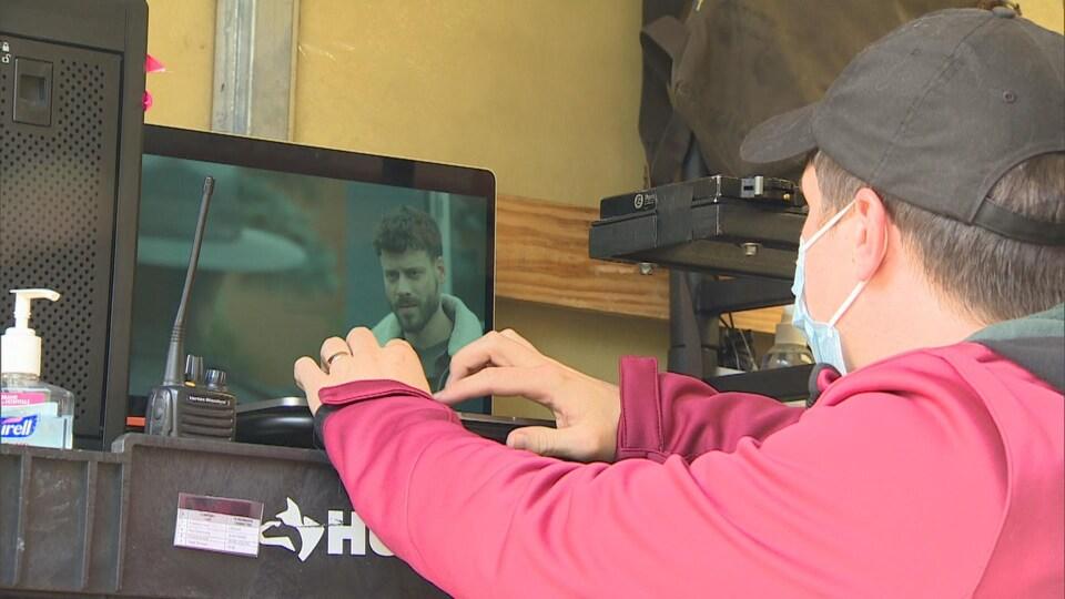 Un technicien de cinéma observe l'écran d'un ordinateur sur lequel se trouve François Arnaud.