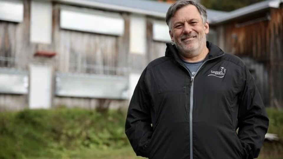 Un homme sourit à la caméra en se tenant debout devant une grange.