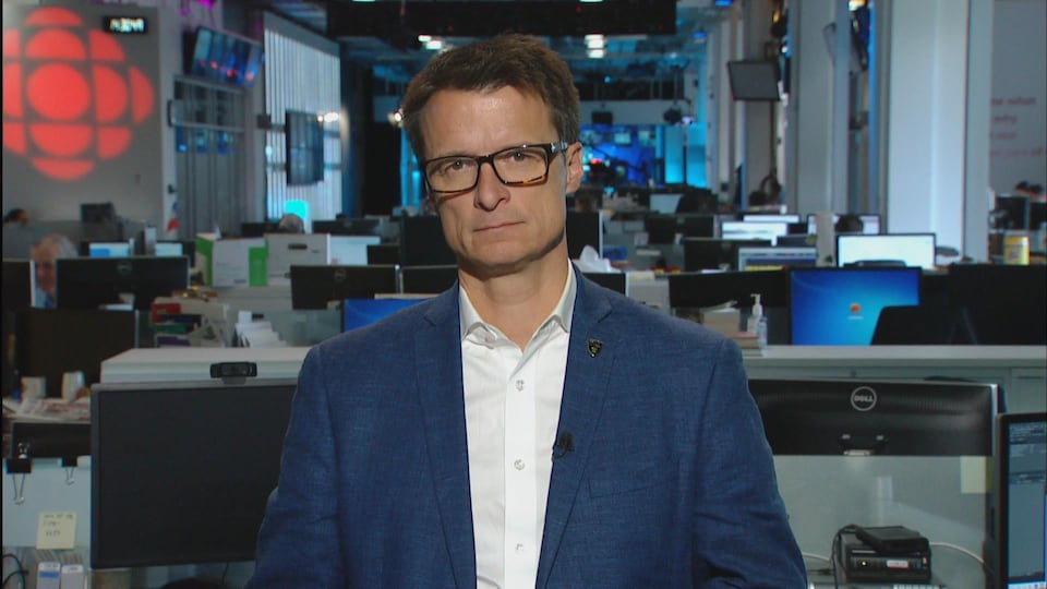 Plan serré de Sylvain Charlebois en entrevue dans une salle de nouvelles.