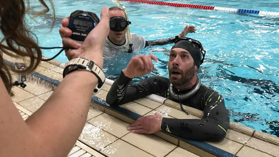 Sylvain Desaulniers dans l'eau, appuyé sur le rebond de la piscine