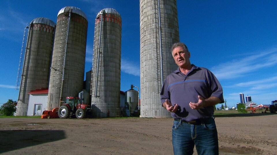 On voit M. Labrecque qui parle à la caméra, devant des bâtiments agricoles.