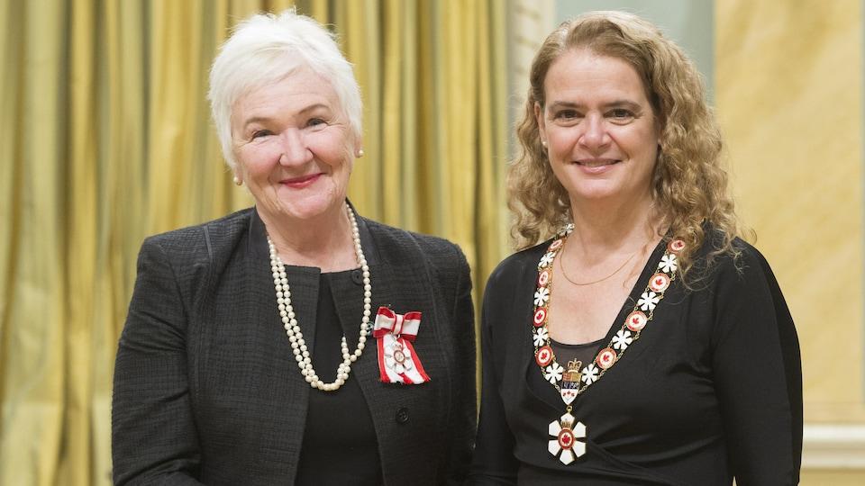 Deux dames, Sylvia L'Écuyer et Julie Payette se sert la main et pause de face.