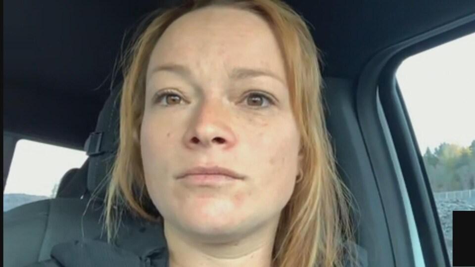Une femme assise dans une voiture.