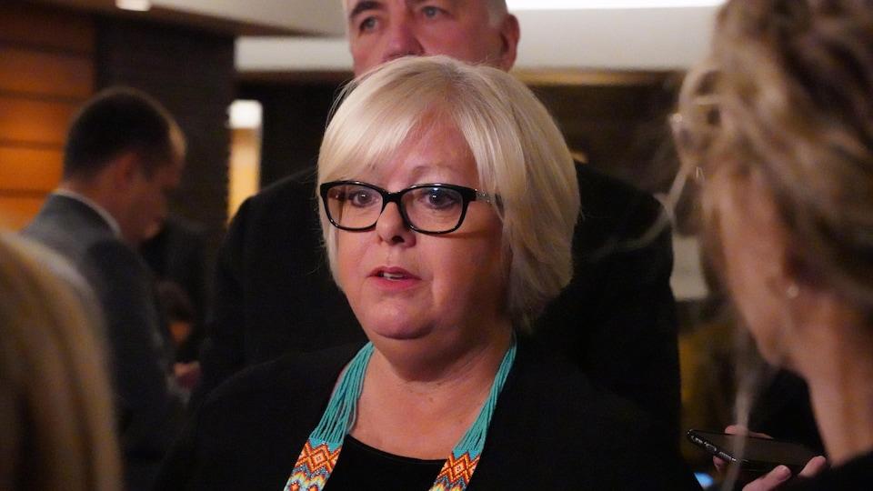 Une dame blonde aux lunettes à bords épais.