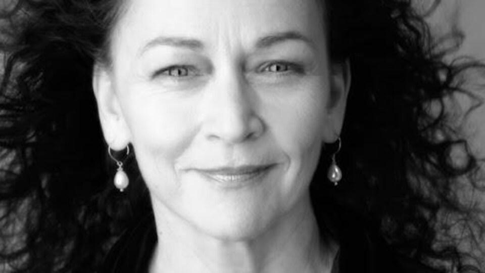Portrait en noir en blanc. Elle porte les cheveux lâchés et des boucles d'oreilles, et elle sourit.