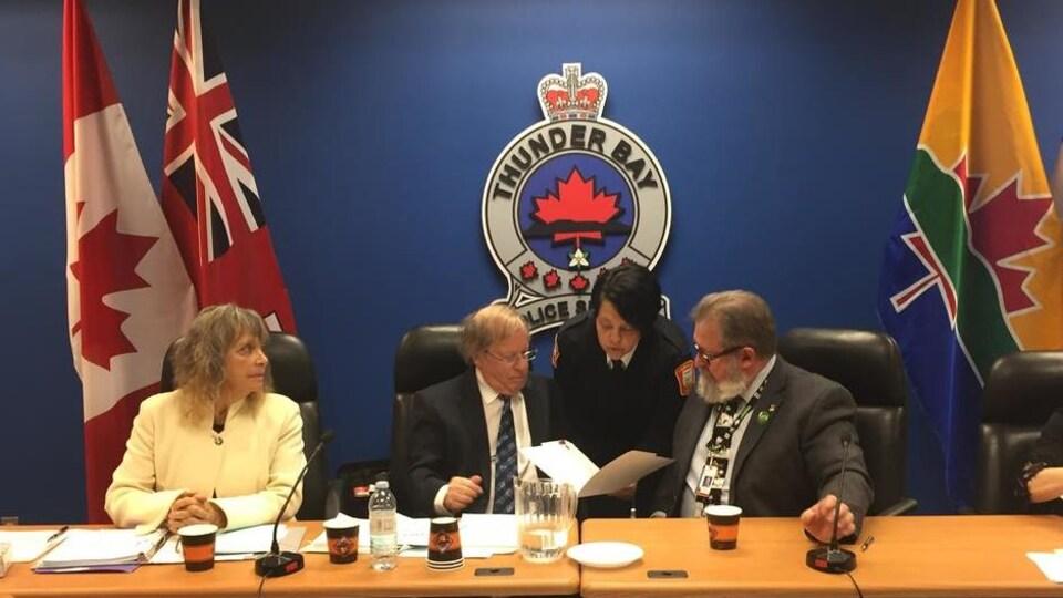 Cinq personnes derrière une table, devant des drapeaux et un logo de la police de Thunder Bay.