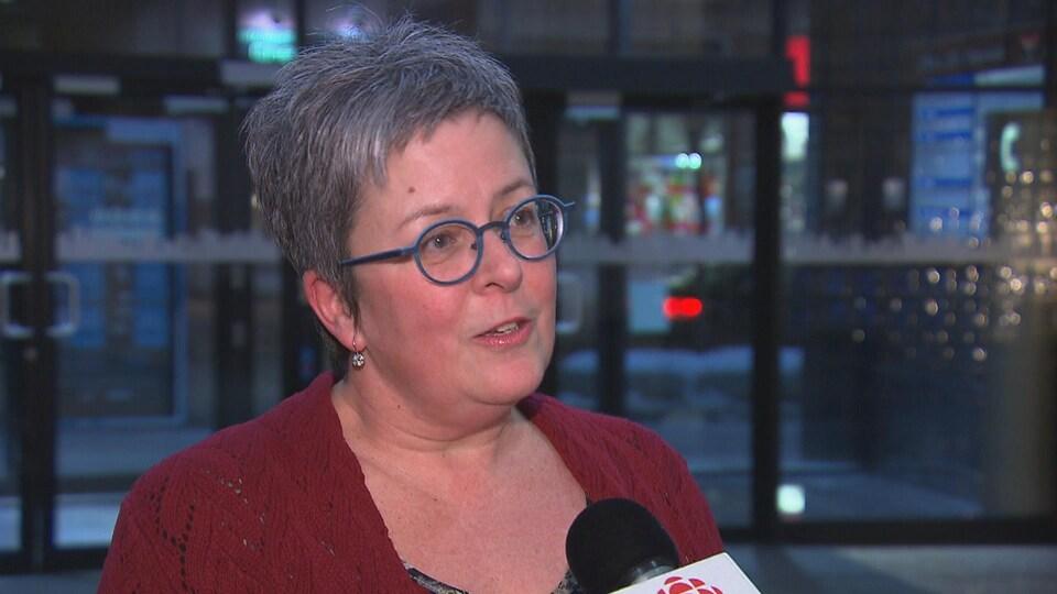 Une femme portant des lunettes bleues et un chandail rouge en entrevue au micro de Radio-Canada