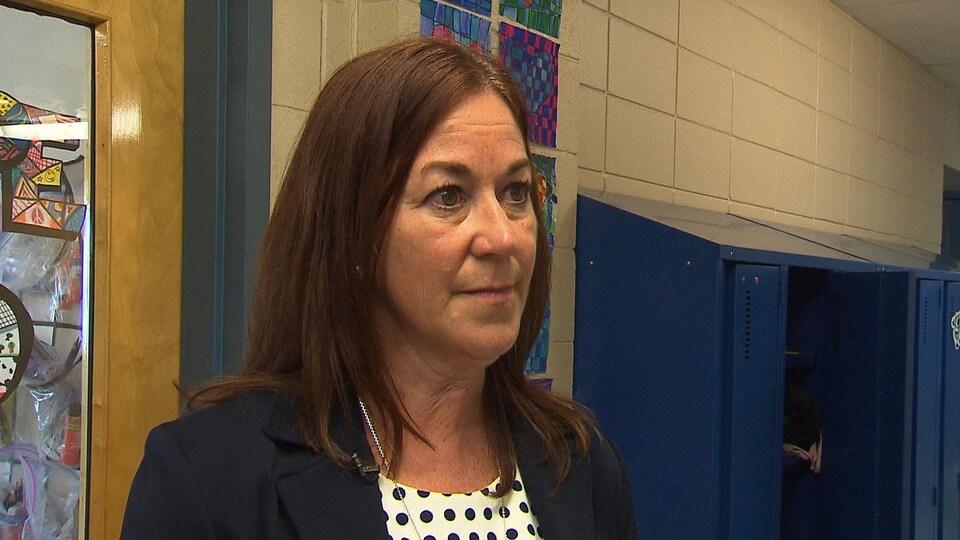 Sylvie Pitre répond aux questions d'un journaliste devant des casiers et la porte d'une classe.