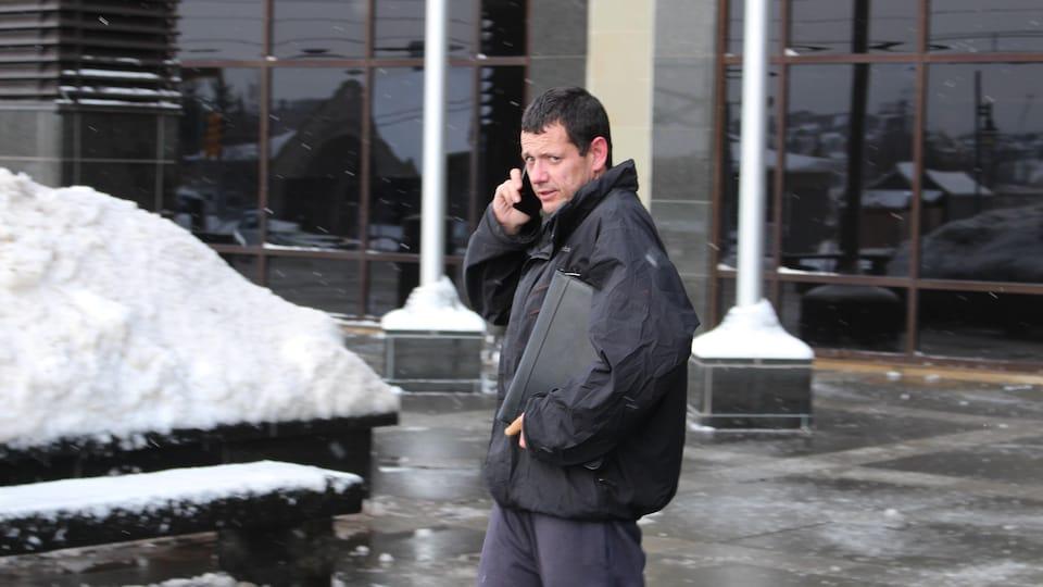 Sylvio Saunier se tient debout devant un palais de justice et parle au téléphone.