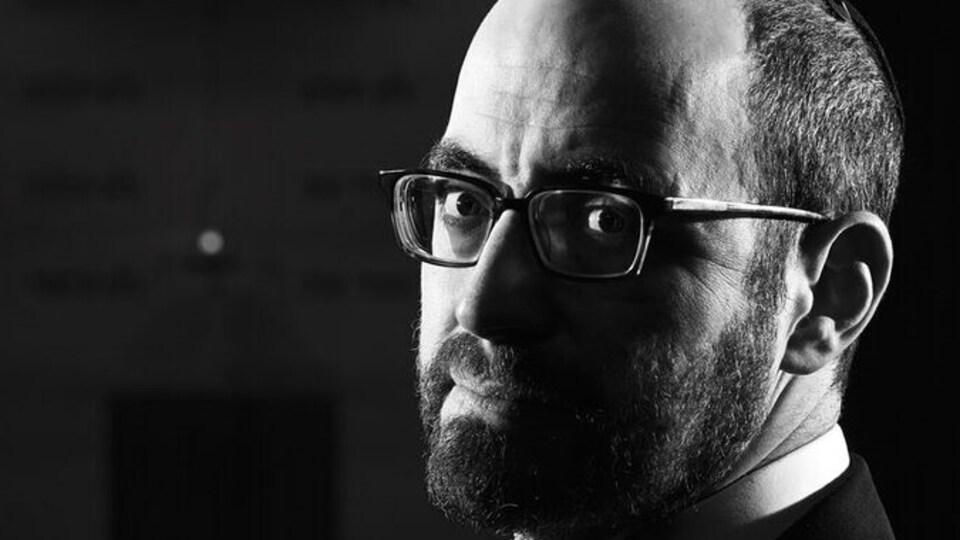 Un homme regarde l'objectif. La photo est en noir et blanc.