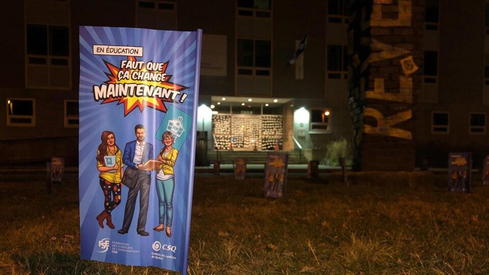 """Une pancarte où on peut y lire """"faut que ça change maintenant"""" posée devant le siège social d'un centre de services scolaire."""