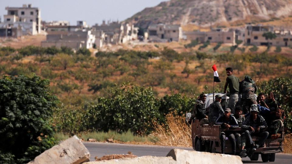 Quelques soldats sont assis dans la remorque d'une camionnette qui roule sur une petite route dans un village de Syrie.