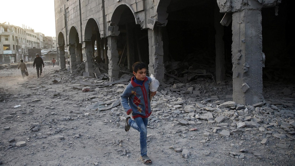 Un garçon syrien court près d'un immeuble endommagé.