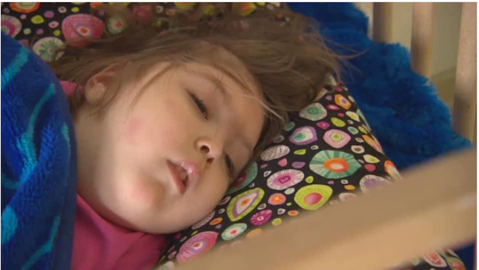 Une petite fille allongée avec les yeux et la bouche légèrement ouverts.