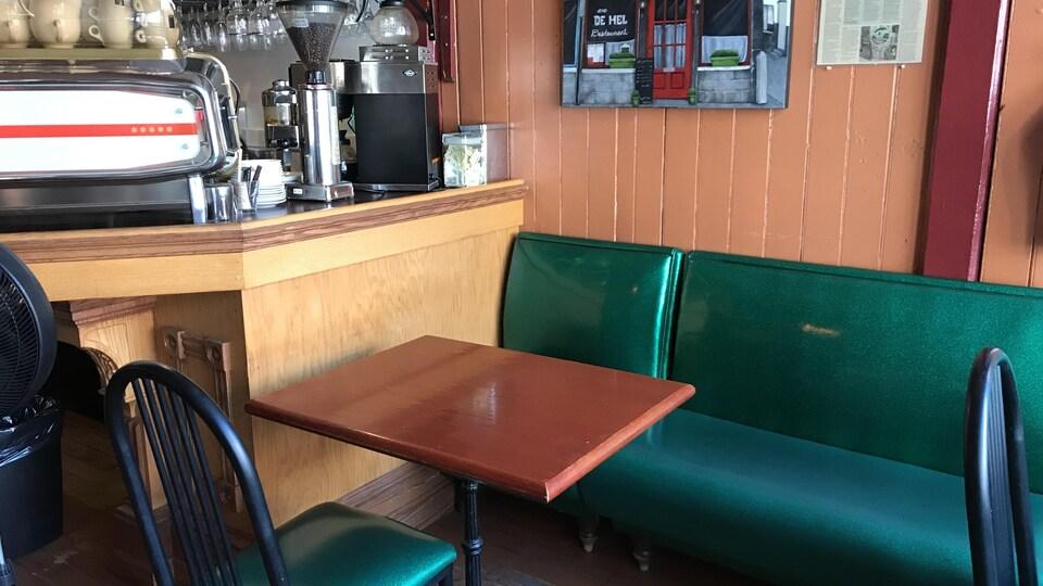 Une banquette et une chaise avec une table au milieu, qui peut asseoir 3 personnes.