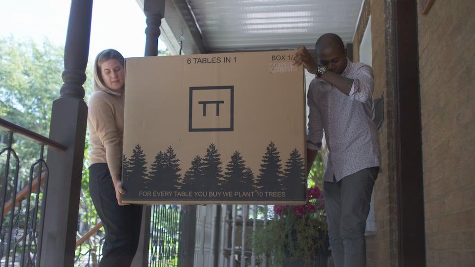 Laurence Morin Rivet et son conjoint entrent dans leur maison avec une grosse boîte contenant une table.