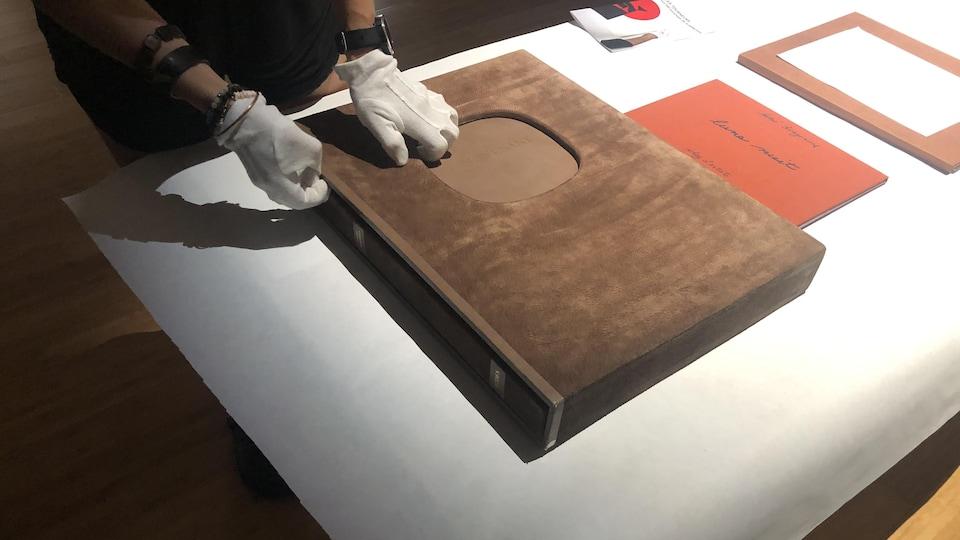 Une personne qui porte des gants blancs s'apprête à ouvrir un livre.