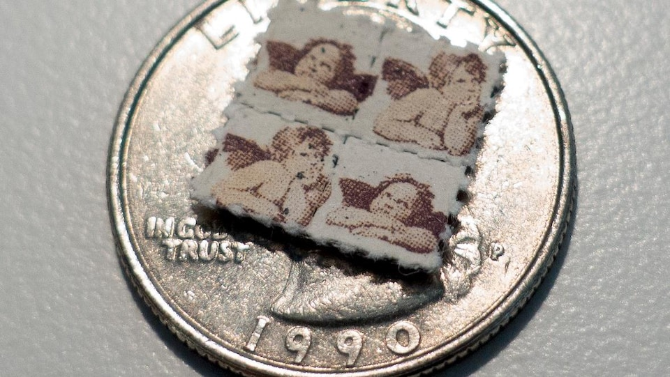 Quatre petits timbres de LSD sont plus petit qu'une seule pièce de 25 sous. Sur les timbres, des images d'anges imprimées.