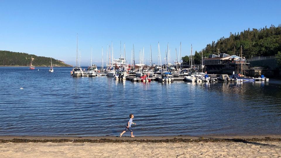 Des bateaux sur l'eau et un enfant qui court sur la plage