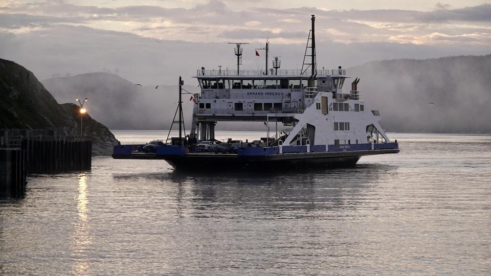 Un navire sur la rivière Saguenay qui arrive bientôt au port, on peut voir de la brume autour du navire.