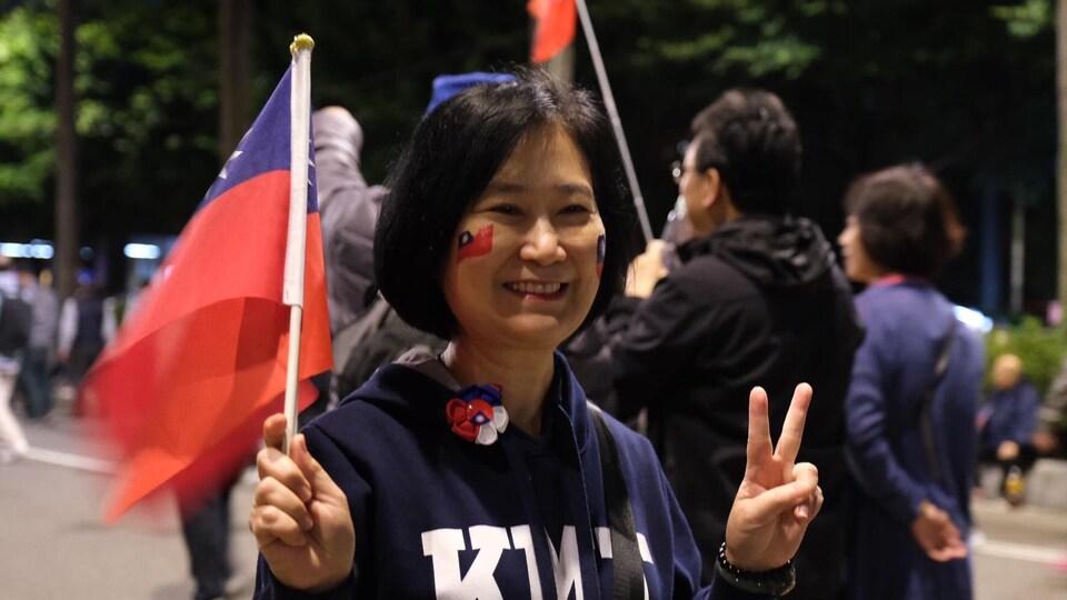 Elle fait le V de la victoire avec sa main gauche.