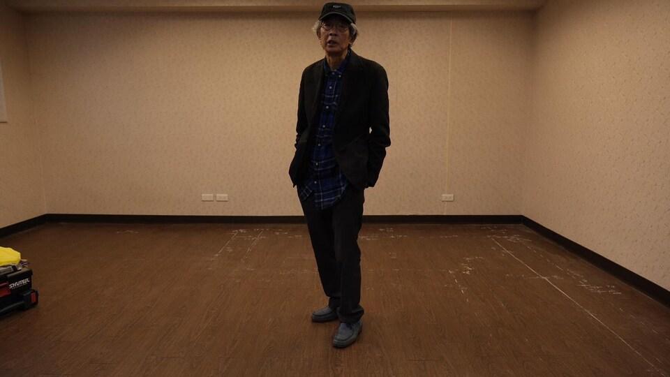 Lam Wing-kee est debout au milieu d'une pièce vide.