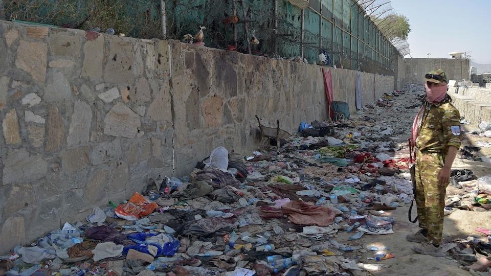 Des débris, des vêtements et des effets personnels jonchent le sol à la suite d'un attentat. Un soldat monte la garde.