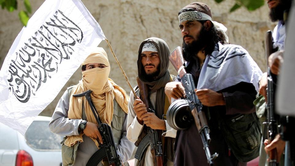 Quatre talibans armés de mitraillettes brandissent un drapeau dans une rue.