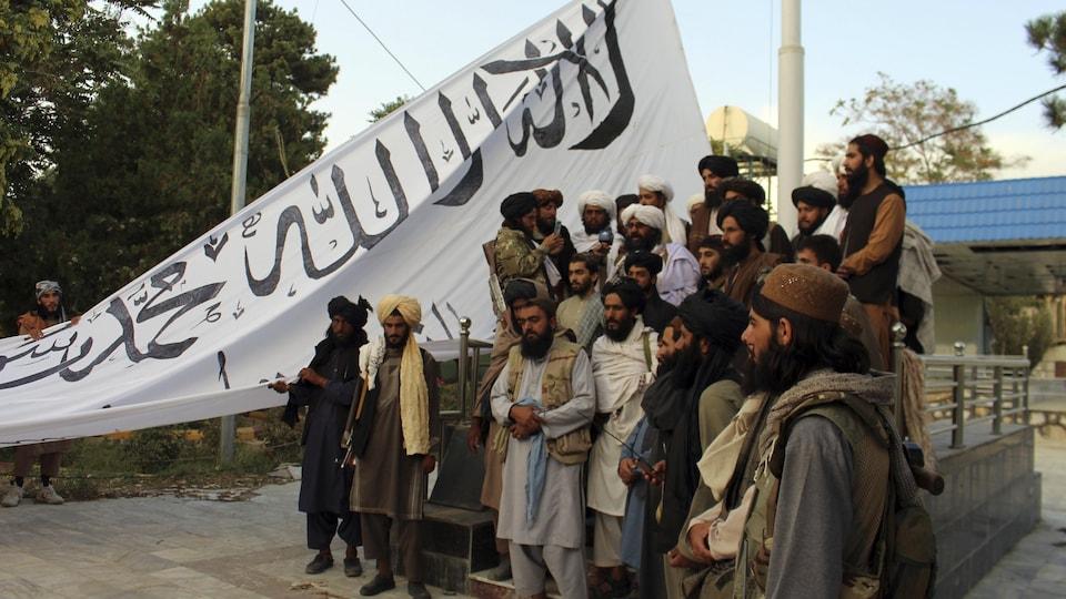 Un grupo de talibanes está de pie y ondea su bandera.