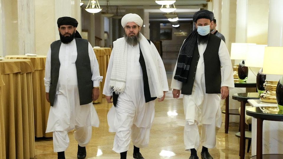 Trois hommes marchent dans un corridor vers la caméra.
