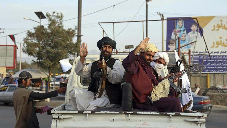 Des combattants talibans armés sont assis dans une camionnette de marque Toyota.