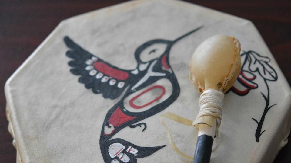 Un tambour autochtone sur lequel un oiseau et une fleur sont dessinés.