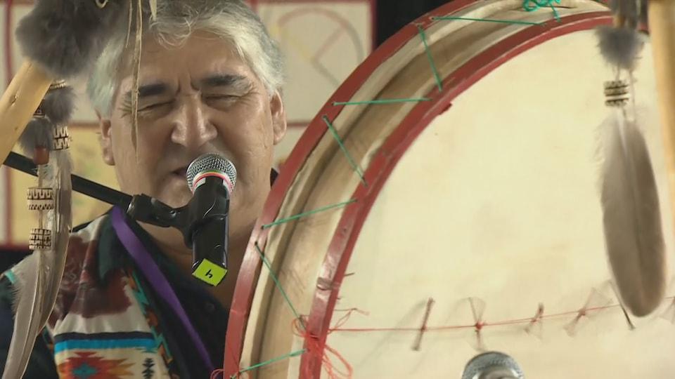 Un Innu joue du tambour traditionnel.